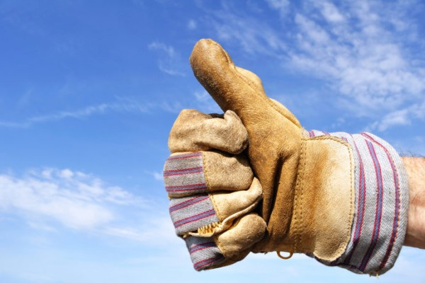 Arbeitshandschuh zeigt den Daumen hoch vor einem blauen Himmel