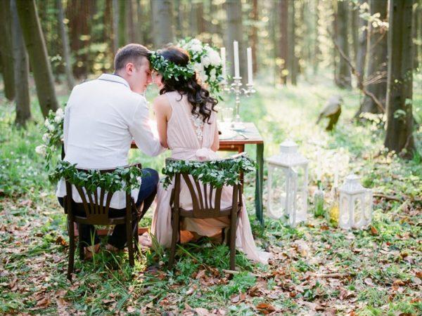 Braut und Bräutigam sitzen an einem Tisch im Wald