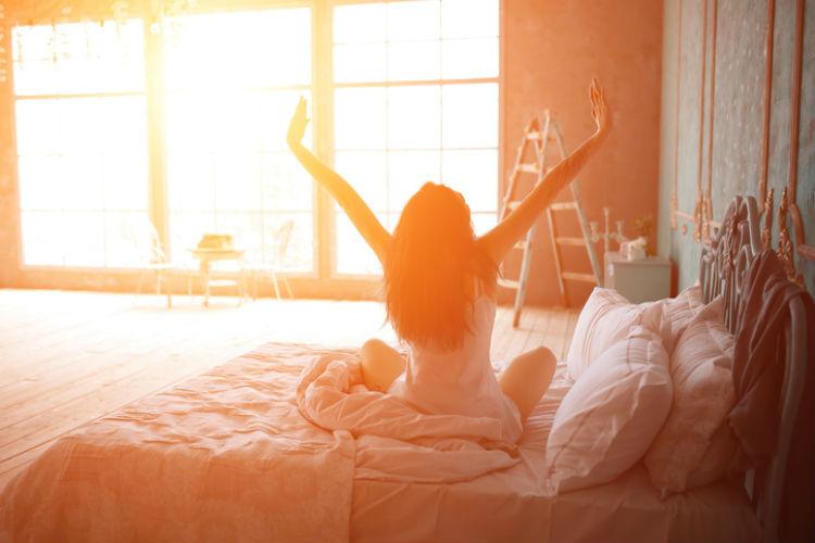 Bettwäsche-Sommer: Frau sitzt auf dem Bett und streckt sich vor einem Sonnenerhelltem Fenster