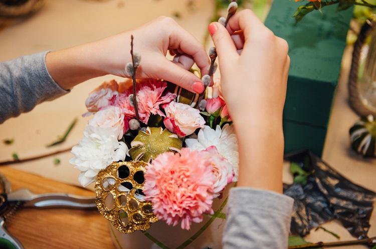 Zwei Hände dekorieren einen Blumenstrauß
