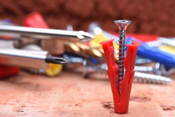 Dübel entfernen - Schraube in rotem Dübel