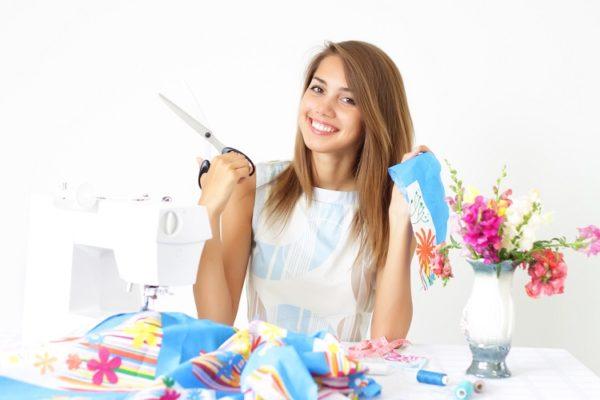 Junge Frau sitzt am Tisch mit Nähmaschine sowie Stoff und Schere in den Händen