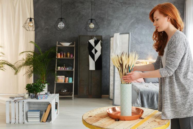 Frau, die das Wohnzimmer dekoriert