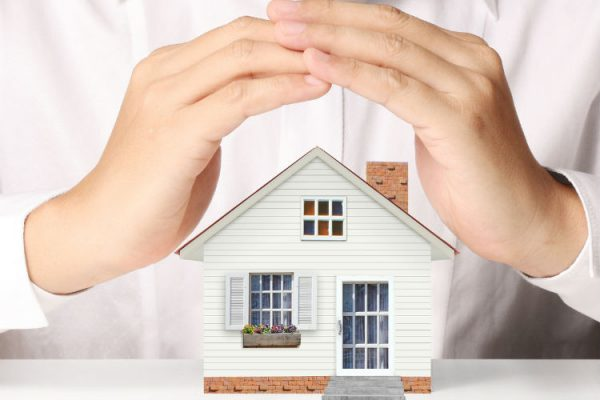 Schützende Hände über einem Haus