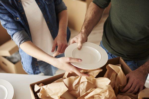 Paar packt Teller aus Umzugskarton