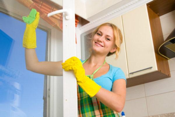 Fenster streifenfrei putzen - Junge Frau putzt Küchenfenster