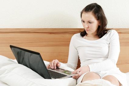 Frau arbeitet im Bett