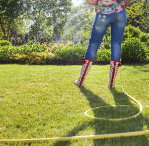 Frau bewässert ihren Garten