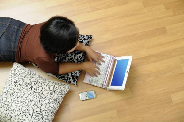 Frau liegt auf Parkett und arbeitet am Laptop