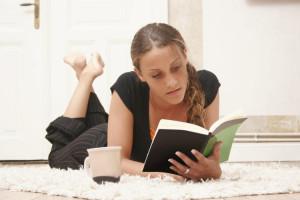 Frau liegt auf einem Flokai Teppich und liest ein Buch