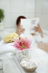 Frau liest in der Badewanne ein Buch