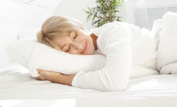 Frau schläft im Bett und ist glücklich