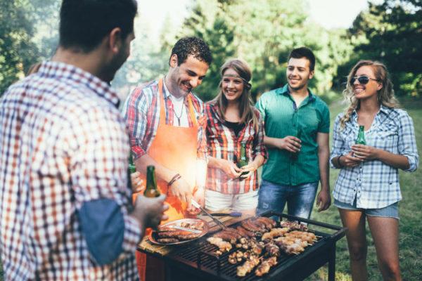 Freunde stehen um einen Grill versammelt der voll mit Grillgut ist