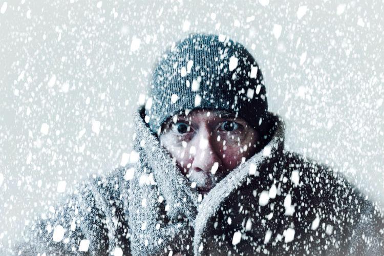 Mann steht im Schnee und freiert