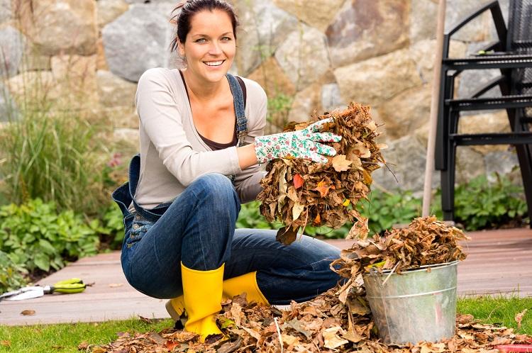 Junge Frau sammelt Herbstlaub auf