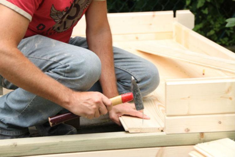 Ein Handwerker baut ein Gartenhaus.