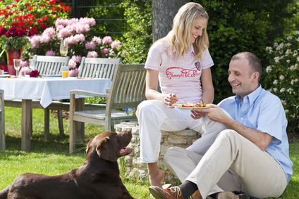 Paar beim essen sitzt mit Hund im Garten