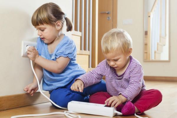Geschwister spielen an einer Steckdose