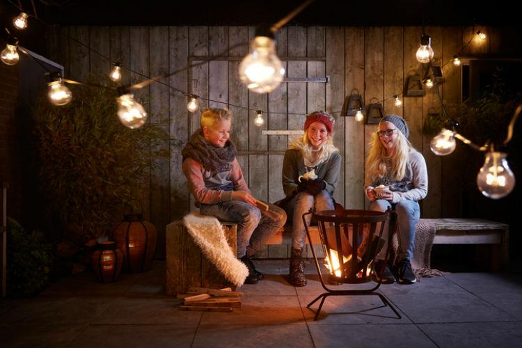Drei Jugendliche sitzen auf einer schön dekorierten Terrasse im Winter an einem kleinen Lagerfeuer