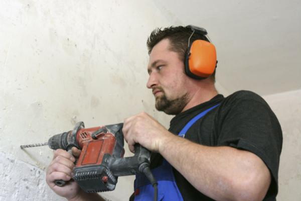 Handwerker bohrt ein Loch in die Wand
