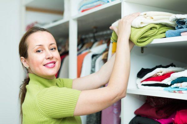 Lächelnde Frau mittleren Alters beim Einräumen des Kleiderschrankes