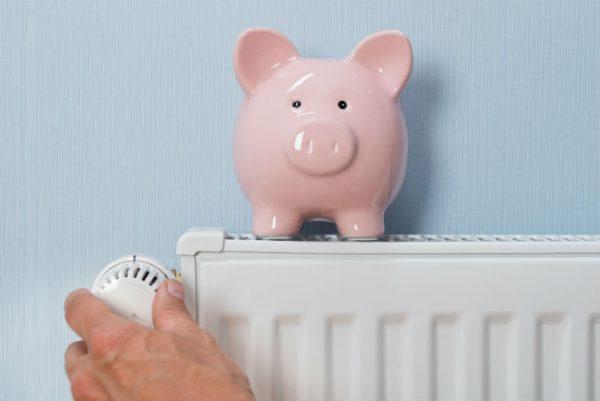 Mann hält Thermostat mit Sparschwein auf Heizkörper