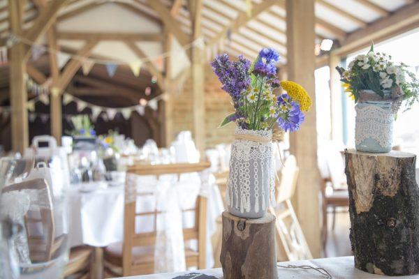 Blumen in Vasen und weißes Hochzeitsambiente