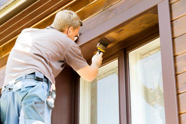 Instandhaltung von Immobilien - Mann streicht Holzfassade & Fenster von außen