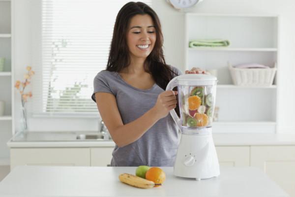 Junge Frau beim Smoothie mixen
