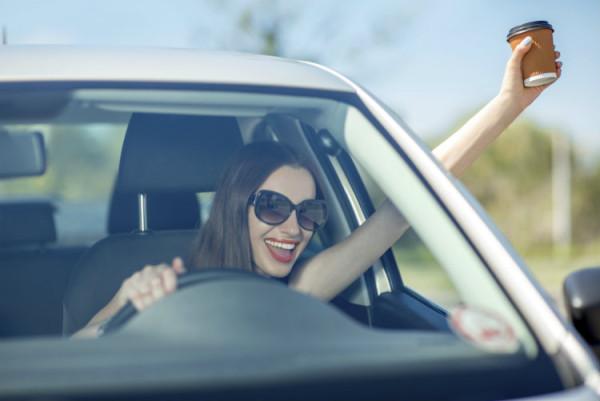 Junge Frau mit Kaffee im Auto