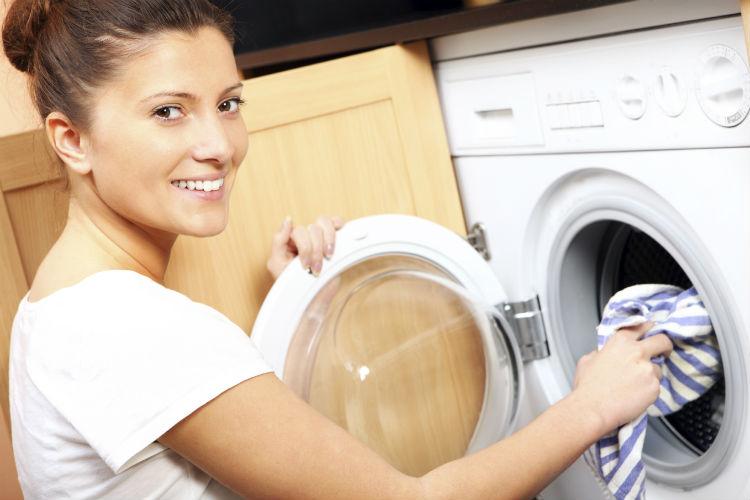 Junge Frau vor der Waschmaschine
