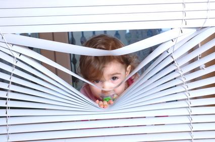 Ein Kind schaut durch eine Jalousie.