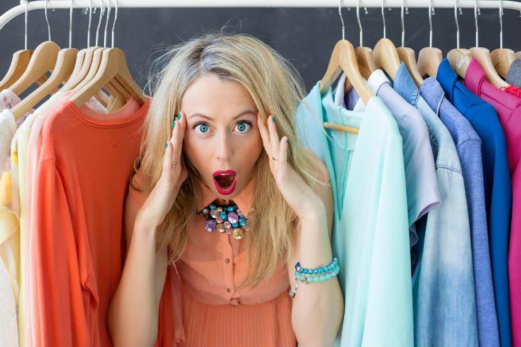 Frau schaut erstaunt aus ihrem Kleiderschrank hinaus