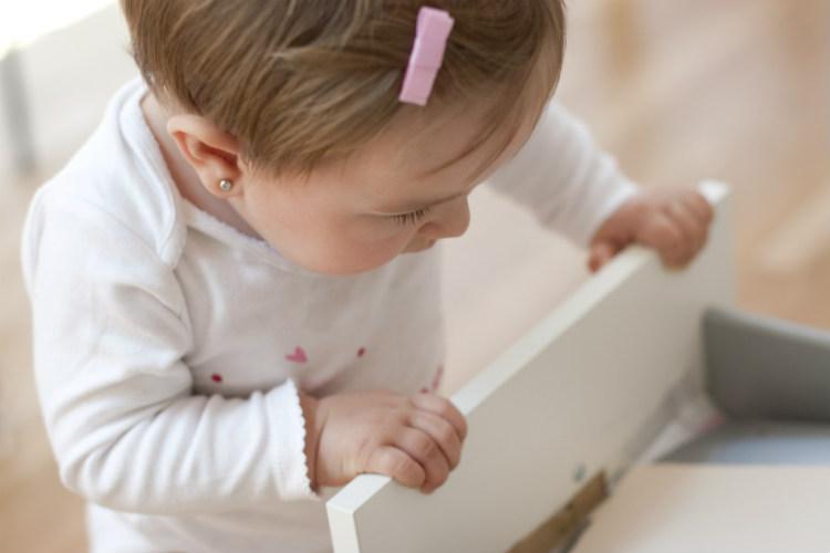 Kleinkind spielt mit einer Schublade