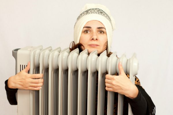 Frau mit Mütze hält Konvektor als zusätzliche Heizung umklammert