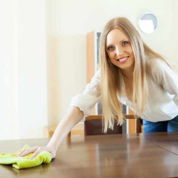 Frau pflegt Holztisch