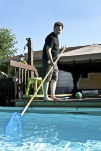 Mann reinigt seinen Pool im Garten