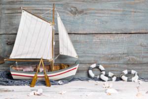 Maritime Wohnungseinrichtung - Modellschiff auf Sand & maritimer Streudeko