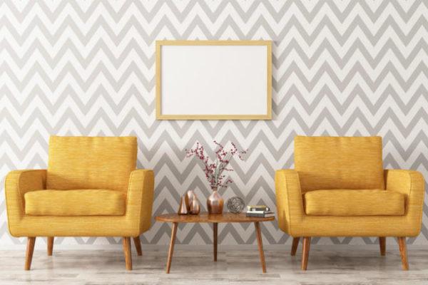 Zwei gelbe Sessel vor einer Tapete im retro-look