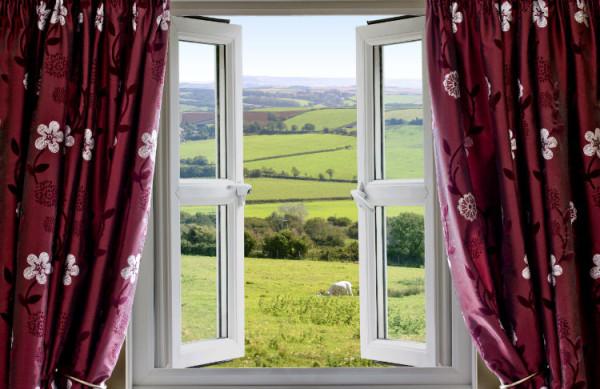 Offenes Fenster mit roten Gardinen