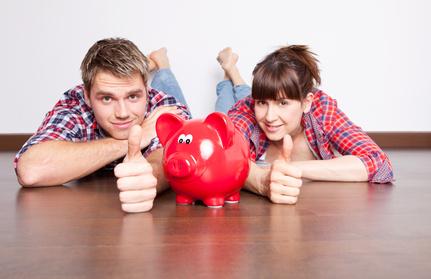 Ein Paar liegt hinter einem Sparschwein.