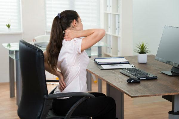 Frau mit verspanntem Rücken am Arbeitsplatz