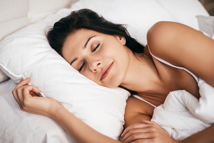 Brunette Frau schläft in weißer Bettwäsche