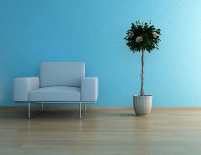 Ein weißer Sessel und eine Blume stehen vor einer blauen Wand.