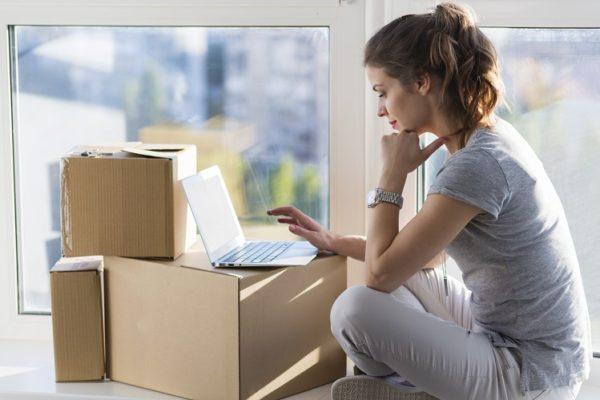Junge Frau sitzt vor Umzugskartons und Laptop