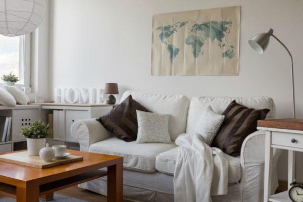 Wohnzimmer mit gemütlichem Sofa, Decke und moderner Dekoration
