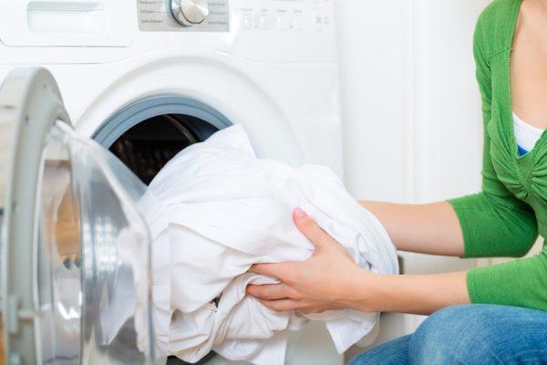 Weißer Vorhang wird in die Waschmaschine gegeben