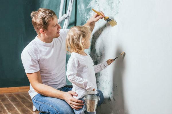 Vater und Tochter streichen mit Öko Farben Wand