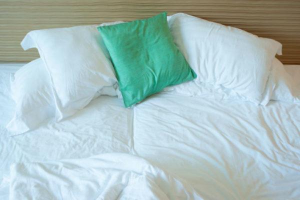 Ein ungemachtes Bett mit Kissen und Decken