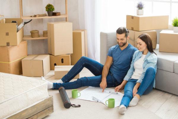 Ein Paar, das in einer Wohnung mit Umzugskartons sitzt und einen Umzug plant